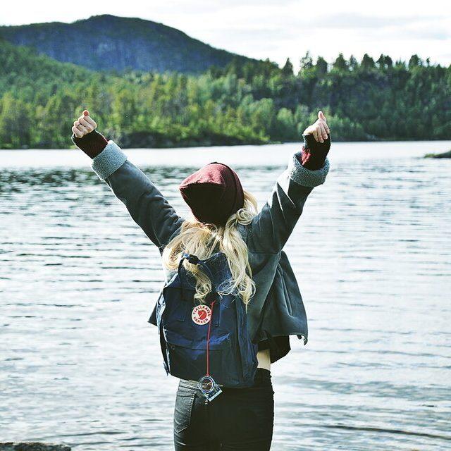 Glad kvinna blickar ut över sjö i norrbotten.